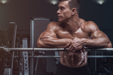 Attractive muscular bodybuilder guy prepare to do exercises with barbell in a gym Banque d'images