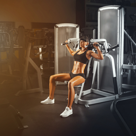 perfect fit: Sport, bodybuilding, lifestyle and people concept. Perfect fit young athletic woman doing exercises on special sport equipment.