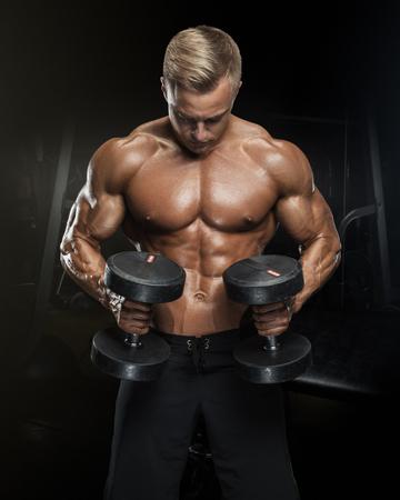 Ajuste perfecto entrenamiento atlético chico con pesas, abdominales perfectos, hombros, bíceps, tríceps y pecho. Hombre hermoso de potencia atlética en la formación de bombeo de los músculos con pesas en un gimnasio. musculoso cuerpo de la aptitud aislado en el fondo oscuro.