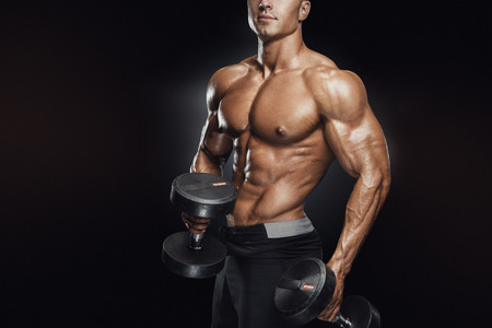 Perfect fit athletic guy workout with dumbbells, perfect abs, shoulders, biceps, triceps and chest. Handsome power athletic man in training pumping up muscles with dumbbells in a gym. Fitness muscular body isolated on dark background.