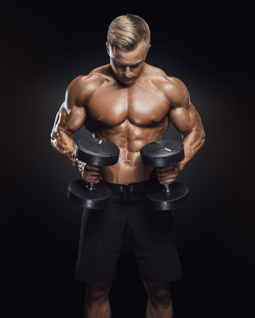 perfect fit: Perfect fit athletic guy workout with dumbbells, perfect abs, shoulders, biceps, triceps and chest. Handsome power athletic man in training pumping up muscles with dumbbells in a gym. Fitness muscular body isolated on dark background.