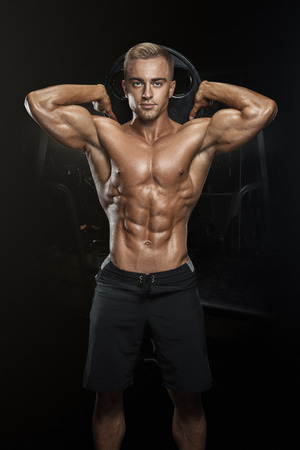 Perfect fit athletic guy posing with barbell plate in gym, perfect lat muscle, shoulders, biceps, triceps and chest. Fitness muscular body isolated on dark background. Banque d'images