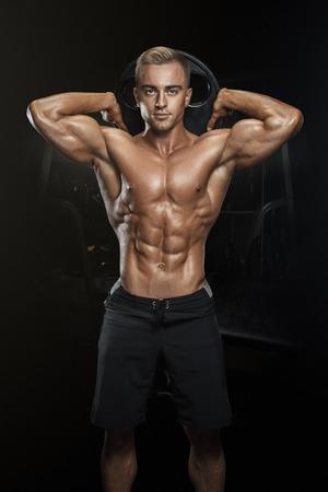 Perfecto chico atlético ajuste que presenta con la placa de pesas en el gimnasio, músculo lat perfecta, hombros, bíceps, tríceps y el pecho. musculoso cuerpo de la aptitud aislado en el fondo oscuro.