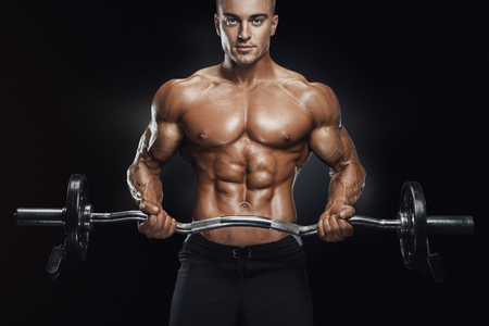 heavy weight: Portrait of handsome bodybuilder performing the biceps curl with EZ curl bar at gym. Perfect physique athletic young man with six pack, perfect abs, shoulders, biceps, lats and chest.