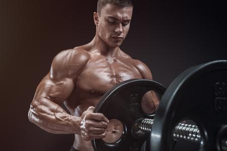 Knappe bodybuilderkerel bereiden om oefeningen met barbell doen in een sportschool, houden barbell plaat in handen Stockfoto