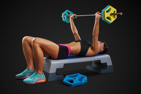 perfect fit: Fitness woman workout with barbell at gym, lie on horizontal position. Perfect fit athletic young woman with six pack, perfect abs, shoulders, biceps, triceps and chest.