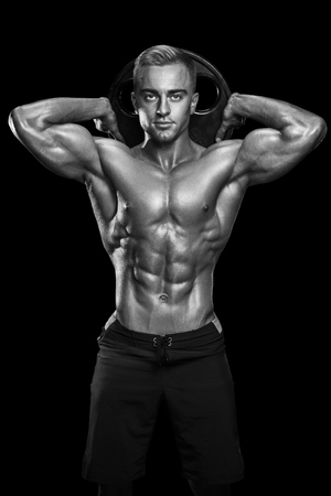perfect fit: Perfect fit athletic guy posing with barbell plate in gym, perfect lat muscle, shoulders, biceps, triceps and chest. Fitness muscular body isolated on dark background. Stock Photo