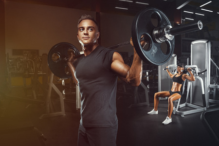 Young and fit couple in the gym doing workout. Group of women and men bodybuilders training on special sport equipment in the gym. Sport, bodybuilding, lifestyle and people concept.