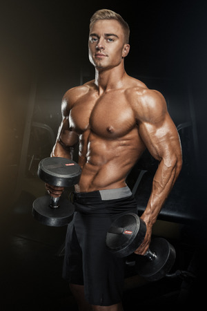man gym: Perfect fit athletic guy workout with dumbbells, perfect abs, shoulders, biceps, triceps and chest. Handsome power athletic man in training pumping up muscles with dumbbells in a gym. Fitness muscular body isolated on dark background.