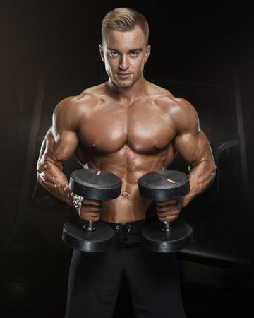 Ajuste perfecto entrenamiento atlético chico con pesas, abdominales perfectos, hombros, bíceps, tríceps y pecho. Hombre hermoso de potencia atlética en la formación de bombeo de los músculos con pesas en un gimnasio. musculoso cuerpo de la aptitud aislado en el fondo oscuro. Foto de archivo - 59714658