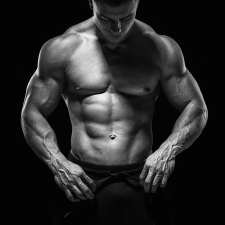 shirtless guy: Handsome athletic guy prepare to do exercises. Isolated image, black background.
