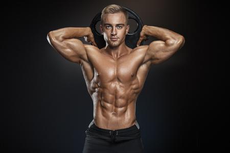 Perfecte pasvorm atletische kerel poseren met barbell plaat in de gymzaal, perfect lat spieren, schouders, biceps, triceps en borst. Fitness gespierd lichaam op een donkere achtergrond.