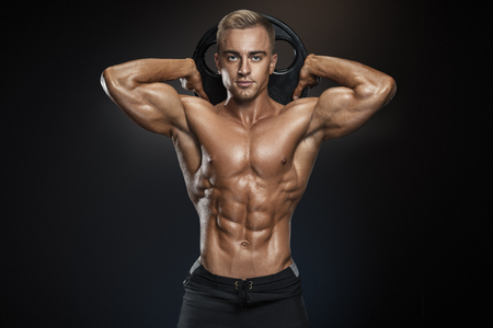 Perfect fit athletic guy posing with barbell plate in gym, perfect lat muscle, shoulders, biceps, triceps and chest. Fitness muscular body isolated on dark background. Standard-Bild