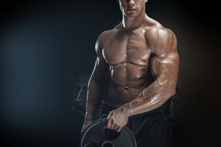 Close up photo of power athletic man doing exercises with barbell plate. Muscular body on dark background.