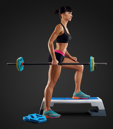 perfect fit: Closeup portrait of beautiful fitness woman workout with barbell at gym. Perfect fit athletic young woman with six pack, perfect abs, shoulders, biceps, triceps and chest. Deadlift barbells workout. Stock Photo