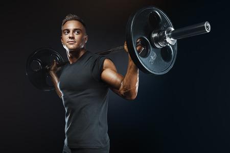 CAMISAS: Closeup retrato de entrenamiento de culturista profesional con barra en fondo negro. Muscular hombre de entrenamiento se pone en cuclillas con los barbells sobre la cabeza