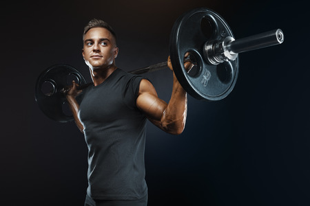 Closeup portrait of professional bodybuilder workout with barbell on black background. Muscular man training squats with barbells over head Standard-Bild