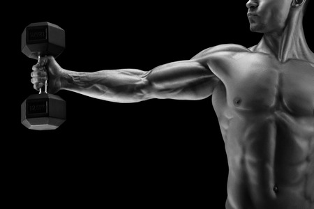 deltoid: Close-up of a power fitness mans hand with dumbbell. Strong bodybuilder with six pack, perfect abs, shoulders, biceps, triceps and chest, deltoid muscle. Black and white photo.