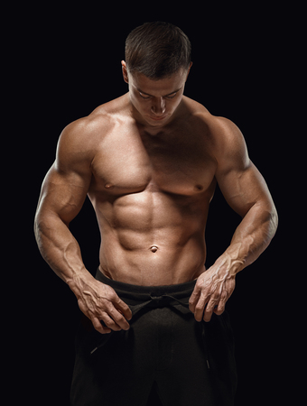 Handsome athletic guy prepare to do exercises. Isolated image, black background.