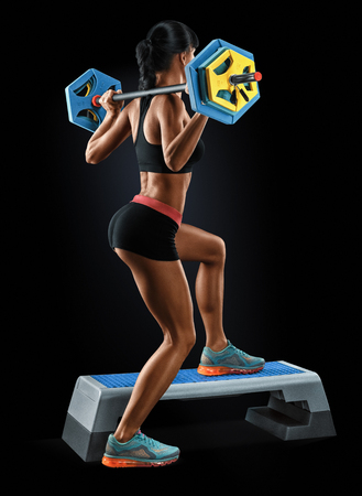 athletic body: Beautiful fitness woman preparing to lift some heavy weights. Strong young woman with beautiful athletic body doing exercises with barbell. Stock Photo
