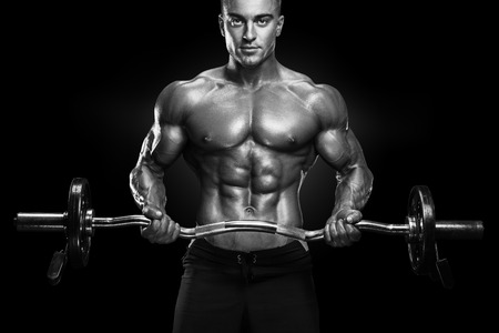 lats: Portrait of handsome bodybuilder performing the biceps curl with EZ curl bar at gym. Perfect physique athletic young man with six pack, perfect abs, shoulders, biceps, lats and chest.