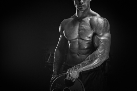 Close up photo of power athletic man doing exercises with barbell plate. Muscular body on dark background. photo