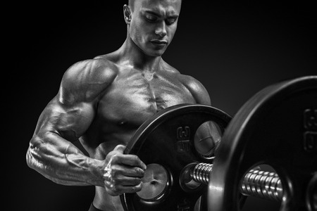 Handsome bodybuilder guy prepare to do exercises with barbell in a gym, keep barbell plate in hands photo