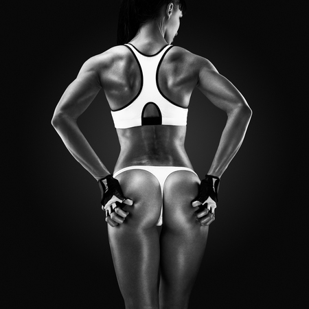 Black and white portrait of fitness athletic young woman showing her well trained body, turned back. Image of fitness woman in sports clothing looking down. Stock Photo