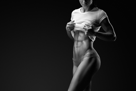 Black and white portrait of young woman with muscular body standing against black background. Image of fitness woman in sports clothing.