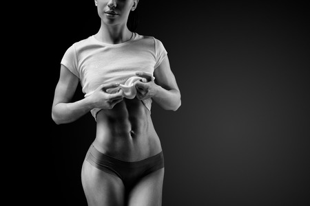 chest hair: Cropped black and white shot of a strong woman with muscular abdomen in sportswear. Fitness female model posing on black background. Beautiful woman with clean and glowing skin isolated on dark background. Stock Photo