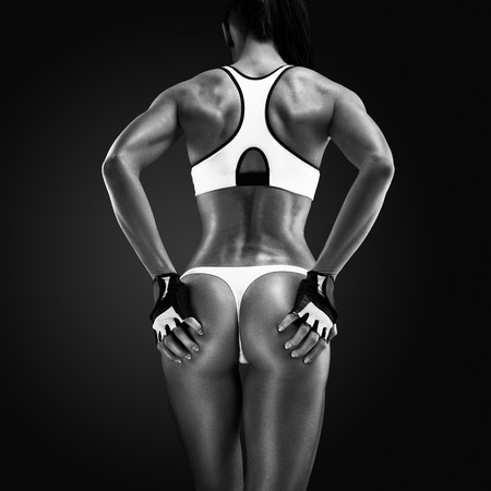 Rear view of fitness female with muscular body. Back of a fit and muscular woman athlete in sports bra.