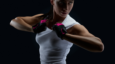Fitness female model in white sporty lingerie, gloves standing on black background confidently looking behind. Female bodybuilder wearing gloves ready for gym exercise. Stock Photo