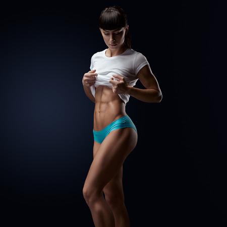 atletismo: Aptitud de la mujer atlética joven que muestra su cuerpo bien formado, paquete de seis, abdominales perfectos, hombros, bíceps, tríceps y el pecho, músculo deltoides. Foto en fondo oscuro con espacio de copia.