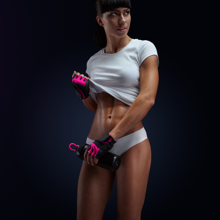 body pump: Young woman in sporty lingerie holding protein shake bottle. Horizontal studio shot with copy space on black background. Stock Photo