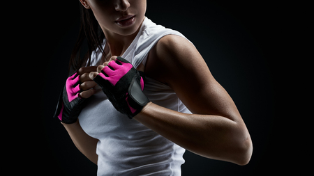 Close up portrait of female bodybuilder wearing gloves ready for gym exercise. Horizontal studio shot with copy space on black background