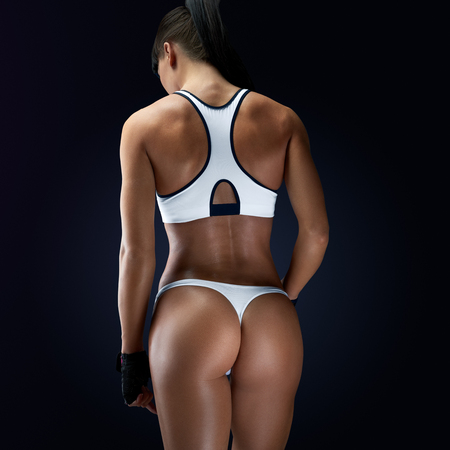 Fitness athletic young woman showing her well trained body, turned back. Image of fitness woman in sports clothing looking down