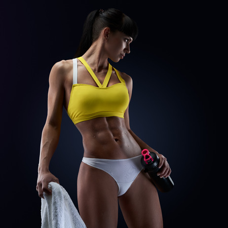 Fitness woman showing her abs, holding protein shake bottle ready for drinking. Close up of young womans torso. Perfect abdomen muscles of a female athlete on black background.