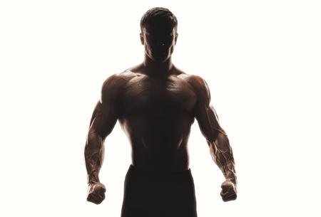 Donkere silhouet van een sterke man op een witte achtergrond. Zekere jonge fitness man met sterke handen en gebalde vuisten. Clipping pad binnen