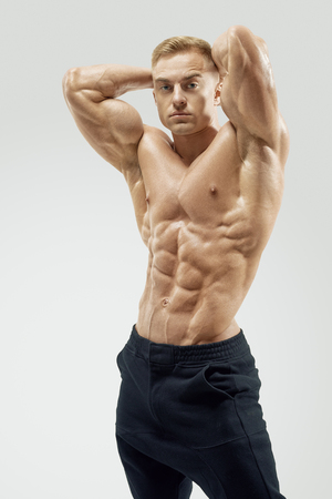 six pack: Shirtless male bodybuilder with muscular build strong abs showing. Shot of healthy muscular young man. Perfect fit, six pack, abs, abdominal muscle, shoulders, deltoids, biceps, triceps and chest. Stock Photo