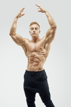 body pump: Shot of healthy muscular young man. Perfect fit, six pack, abs, abdominal muscle, shoulders, deltoids, biceps. Shirtless male bodybuilder with muscular build strong abs showing rising hand.