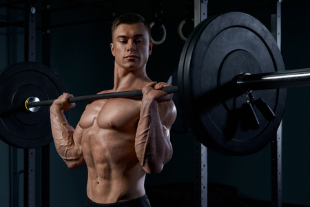 Handsome bodybuilder doing exercise with a barbell at gym. Determined male athlete lifting heavy weights. Man doing a lifting workout on dark background photo