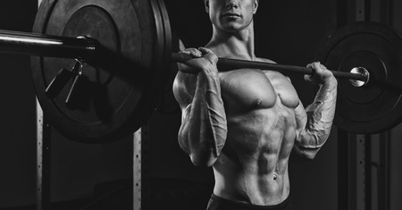 Black and white close up photo of man doing a lifting workout on dark background at gym. Determined male athlete lifting heavy weights. photo