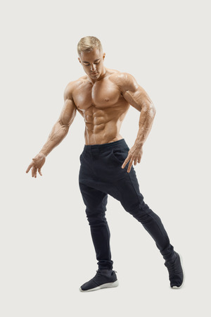 Full-length shot of handsome young man with muscular body standing against white background. Perfect fit, six pack, abs, abdominal muscle, shoulders, deltoids, biceps. Vector mask clipping path Stock Photo