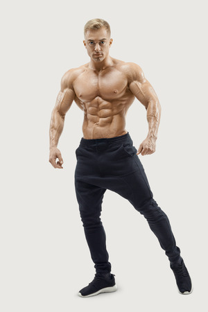 Portrait of young athletic man with muscular physique. Shirtless male model standing confidently against grey background. Perfect fit, six pack, abs, abdominal muscle, shoulders, deltoids, biceps.