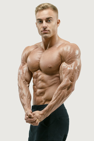 six pack: Perfect fit, six pack, abs, abdominal muscle, shoulders, deltoids, biceps, chest. Bodybuilder with muscular physique looking at camera showing both hands muscles. Vector path mask clipping Stock Photo