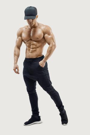 Retrato de cuerpo entero de culturista masculino descamisado que presenta con la estructura muscular abdominales fuertes que muestra el modelo masculino de la aptitud joven masculino posando sin camisa contra el fondo blanco. Vector trazado de máscara de recorte Foto de archivo - 67336494