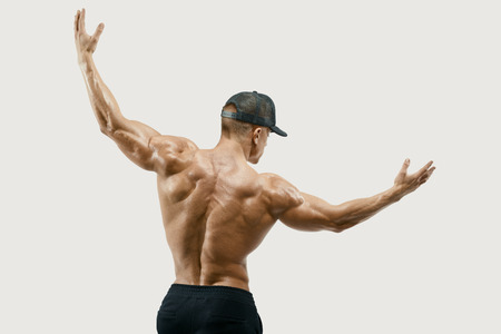 six pack: Shot of healthy muscular young man turning back and rise both hands. Perfect fit, six pack, abs, abdominal muscle, shoulders, deltoids, biceps. Vector path clipping mask