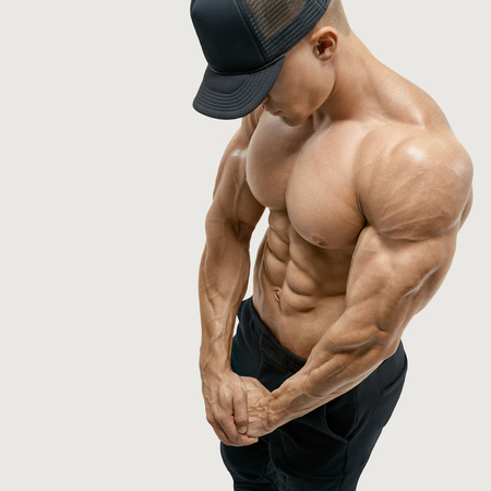 Shirtless male with muscular build strong abs showing. Perfect fit, six pack, abs, shoulders, deltoids, biceps. Bodybuilder in black cap with muscular physique looking down. Vector clipping mask path