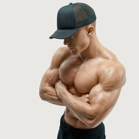 Shot of healthy muscular young man with black beseball cap. Perfect fit, six pack, abs, abdominal muscle, shoulders, deltoids, biceps. Shirtless male bodybuilder with muscular build cross hands.
