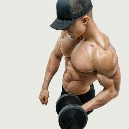 sportsmen: Closeup of a handsome power athletic man bodybuilder doing exercises with dumbbell in left hand.  Isolated over white background. Wearing a black baseball cap. Vector path clipping mask